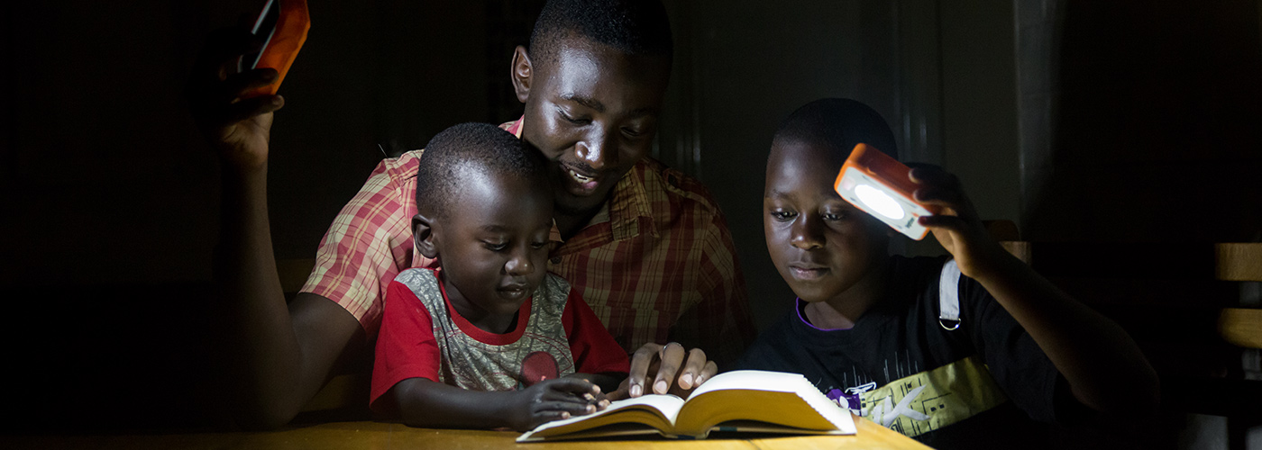 Family in Suubi, Uganda reading with solar lights © SolarBuddy.org / WWF-Aus